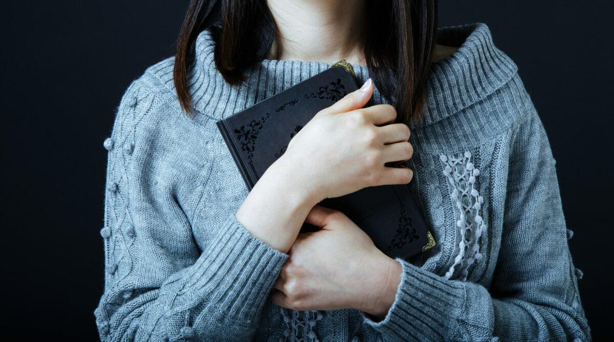 ノートを抱きかかえる女性